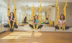 Group of young women doing aerial yoga exercise or antigravity yoga in fitness studio. Fitness, stretch, exercise and healthy lifestyle people. Woman using hammock.