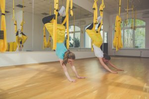 Two girls doing aerial fly yoga exercise or antigravity yoga in fitness studio. Flying, fitness, balance, exercise and healthy lifestyle people. Woman using yellow hammocks for stretching